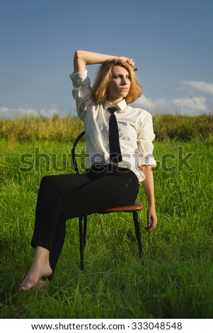 Beauty woman sitting in the armchair at the field and looking in expanse