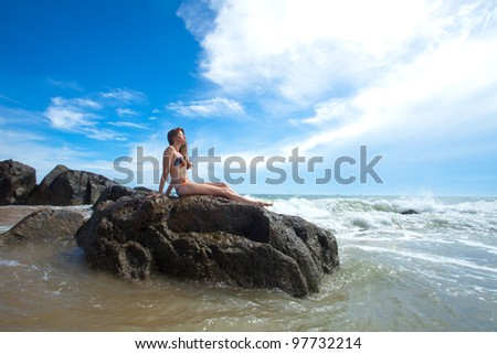 Beauty woman sitting on rock in amazing tropical ocean - stock photo