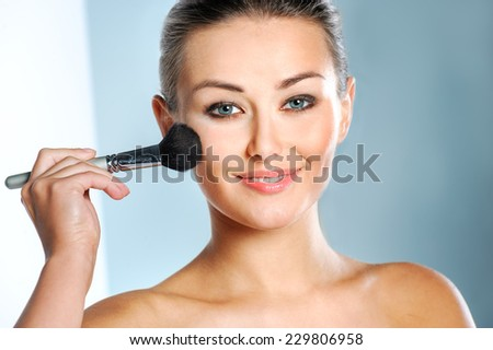 Beauty Woman. Skincare concept. Beauty Face. Beauty concept.Makeup Applying. Professional Make-up.Beauty Fashion Girl Applying skin powder. - stock photo