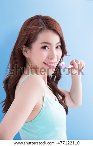 beauty woman take toothbrush and smile to you with blue background, asian