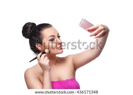 Beauty woman taking a selfie while putting make-up on