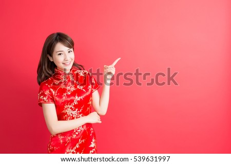 beauty woman wear cheongsam and show something to you in chinese new year