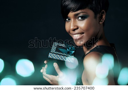 beauty woman with a present with a bokeh below - stock photo