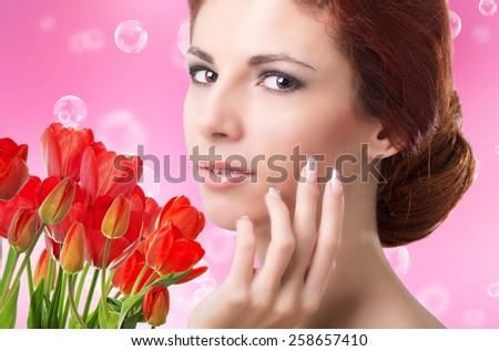 Beauty Woman with Beautiful garden fresh red tulips - stock photo