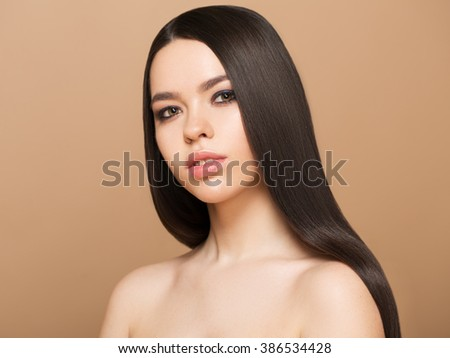 Beauty Woman with beautiful make up and healthy smooth brown hair. Attractive Fashion Model with Long and Healthy Brown Hair. Beauty Brunette Girl on brown background - stock photo
