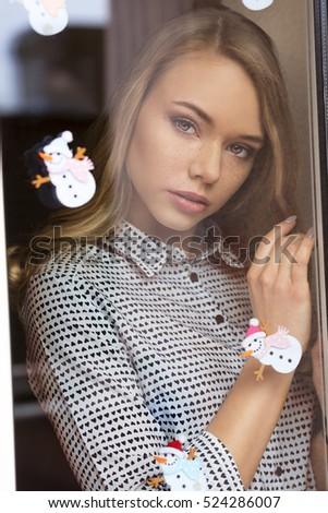 beauty woman with blonde long hair and freckles in romantic pose behind window pane decorated with small snowman stickers . Lovely portrait in winter atmosphere