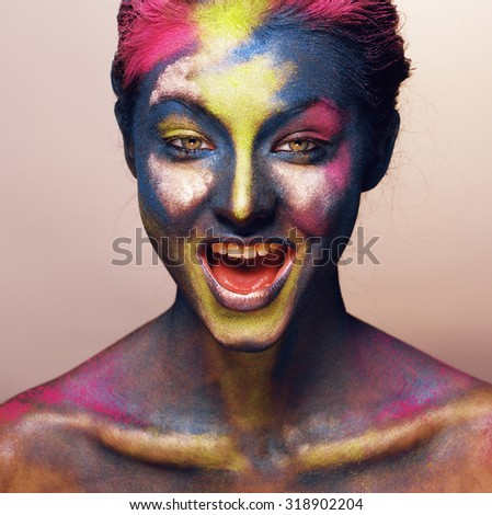 beauty woman with creative make up like Holy celebration in India closeup smiling cool