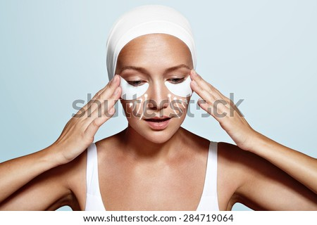 beauty woman with eye patches and lines showing an effect of