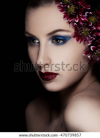 Beauty woman with flowers on black background.Fashion portrait.Head shot. Creative portrsit.