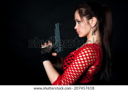 Beauty woman with gun on black background - stock photo