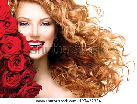 Beauty woman with long curly red hair and beautiful red roses hairstyle. Fashion model girl with blowing healthy wavy hair isolated on white background. Glamour lady portrait with red roses bouquet - stock photo
