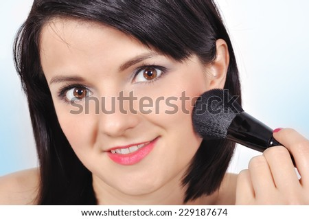 Beauty woman with makeup brush - stock photo