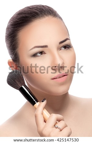 Beauty woman with Makeup Brushes. Natural Make-up for Brunette girl with Brown Eyes. Beautiful Face. Makeover. Perfect Skin. Applying Makeup - stock photo