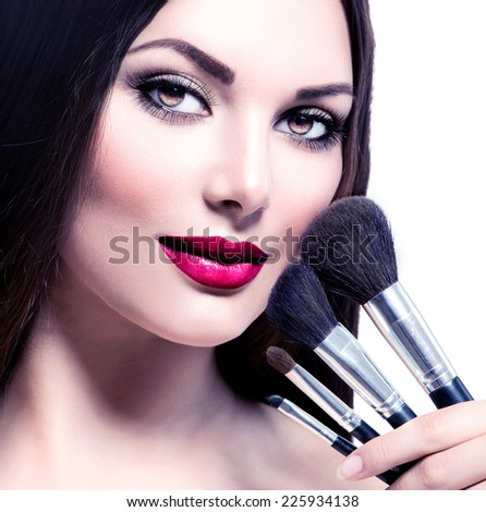 Beauty Woman with Makeup Brushes. Natural Make-up for Brunette Lady with Brown Eyes. Beautiful Face. Makeover. Perfect Skin. Applying Holiday Makeup with red lipstick - stock photo