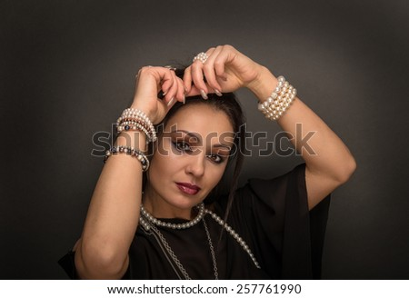Beauty woman with pearls on the dark background - stock photo