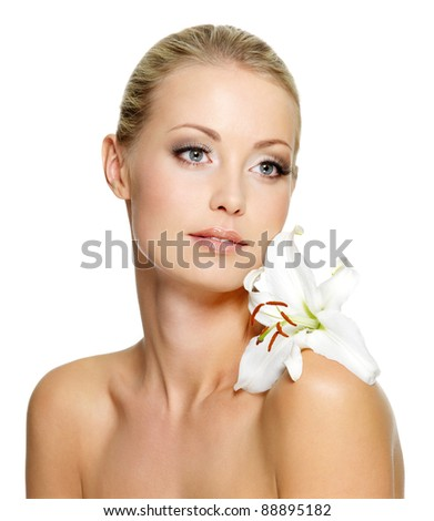 Beauty woman with perfect clean skin and lily flower on shoulder - isolated