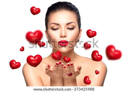 Beauty Woman with perfect make up Blowing Valentine hearts. Valentine's Day Beautiful Fashion sexy Girl showing copy space on the open hands. Gestures for advertisement