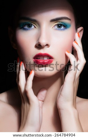Beauty Woman with Perfect Makeup. Beautiful Professional Holiday Make-up. Purple Lips and Nails. Beauty Girl's Face isolated on Black background - stock photo