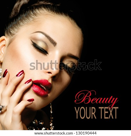 Beauty Woman with Perfect Makeup. Beautiful Professional Holiday Make-up. Red Lips and Nails. Beauty Girl's Face isolated on Black background - stock photo