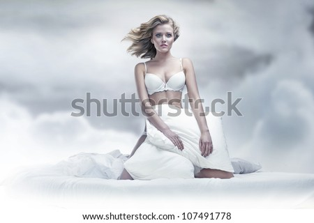 Beauty woman with pillow over sky background - stock photo