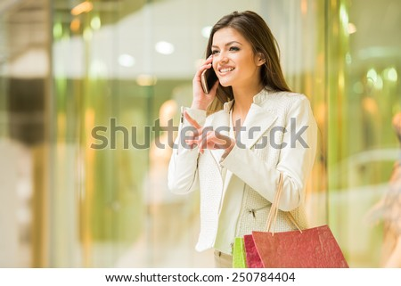 Beauty woman with shopping bags in shopping mall is talking by phone. Sales. Shopping Center. - stock photo
