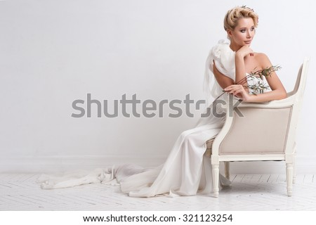 Beauty woman with wedding hairstyle and makeup. Bride fashion. Jewelry and Beauty. Woman in white dress,perfect skin, blond hair. Girl with stylish haircut. .Wedding decoration. Bride with flowers - stock photo