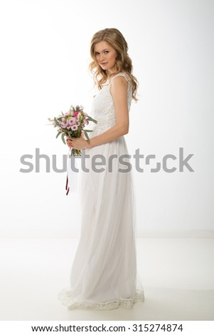 Beauty woman with wedding hairstyle and makeup. Flowers in hands. Bride fashion. Woman in white dress,perfect skin, blond hair. Girl with stylish haircut. - stock photo