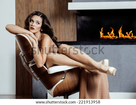 beauty yong brunette woman sitting near fireplace at home, winter warm evening in interior - stock photo