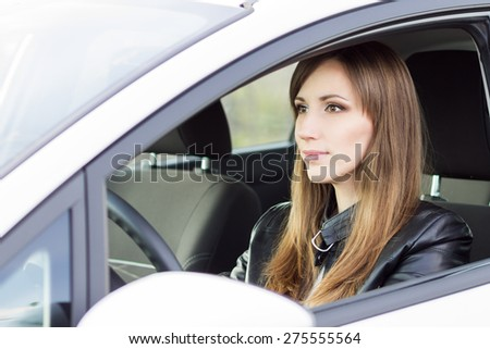 Beauty young business woman in a white car. Smiling caucasian girl in leather jacket drive holding wheel - stock photo