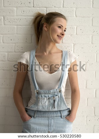 beauty young caucasian woman in blue denim overalls and a white T-shirt front of brick wall
