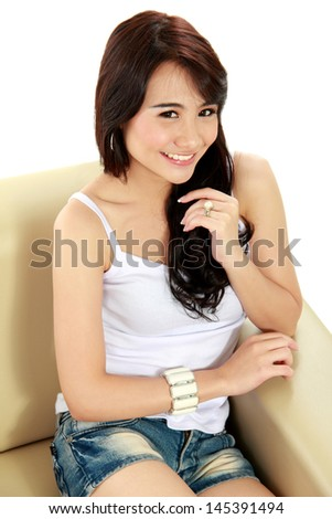 Beauty young girl sitting on sofa and looking at camera