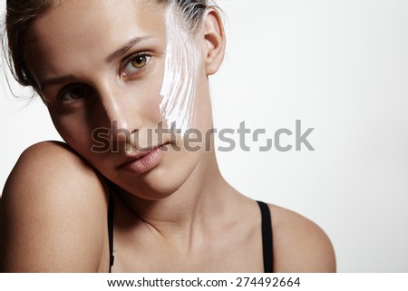 beauty young girl with a white cream on a cheek - stock photo