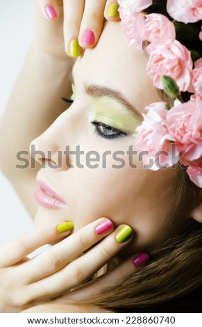 Beauty young real woman with  pink flowers and make up closeup - stock photo