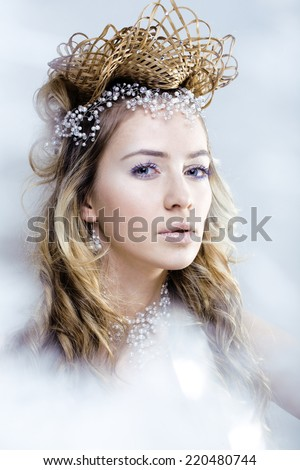 beauty young snow queen in fairy flashes with hair crown on her head - stock photo