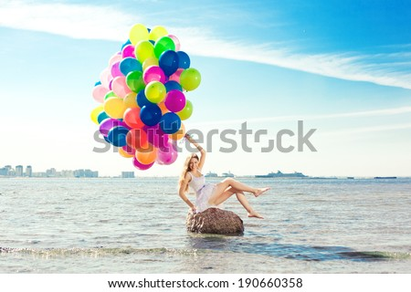 Beauty young stylish woman with colored rainbow balloons in hands against the sky. Positive girl on nature. Smiling woman outdoors enjoying. - stock photo