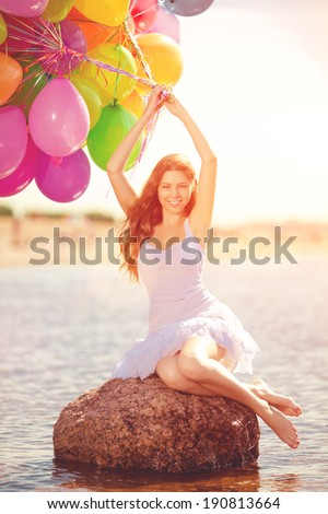 Beauty young stylish woman with colored rainbow balloons in hands against the sky. Positive girl on nature. Smiling woman outdoors enjoying.