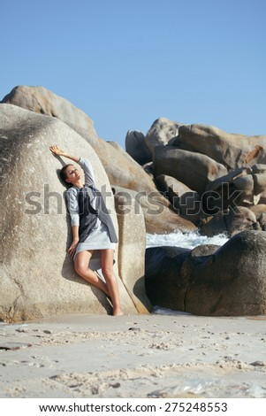 beauty young woman among rocks at sea dreaming relaxing, fancy clothes