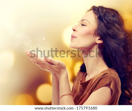 Beauty Young Woman Blowing Magic Dust with stars from her Hands. Holiday Concept. Beautiful Girl. Miracle. - stock photo