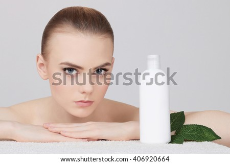 beauty young woman cares for face skin.beautiful girl with cosmetic cream - stock photo