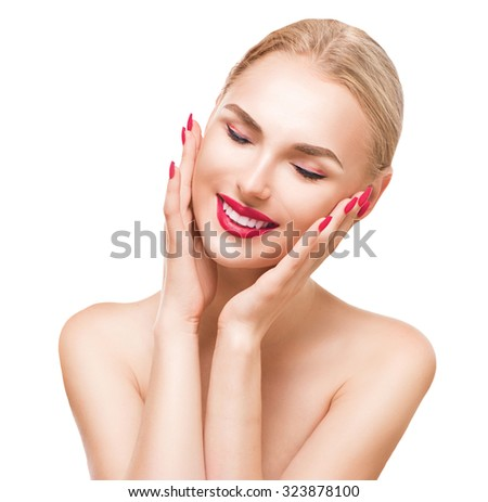 Beauty young woman isolated on white. Beautiful model girl with beauty makeup, red lips and red manicure, perfect fresh skin. Attractive Blonde lady touching her face and smiling. Youth and Skin Care - stock photo