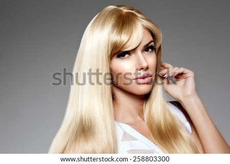 Beauty young woman, luxury long blond hair. Haircut, fringe. Girls fresh healthy skin, makeup, lips, eyelashes, manicured nails shiny. Fashion model in spa care salon. Sexy trendy hairstyle look. - stock photo