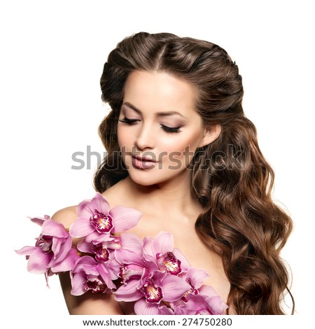 Beauty young woman, luxury long curly hair with orchid flower. Haircut. Beautiful girls fresh healthy skin, makeup, lips, eyelashes. Fashion model in spa care salon. Sexy trendy hairstyle look. - stock photo