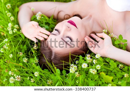 Beauty young woman lying on the grass and dreaming