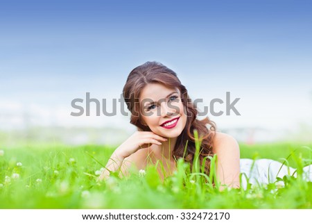 Beauty young woman lying on the grass and smiling - stock photo