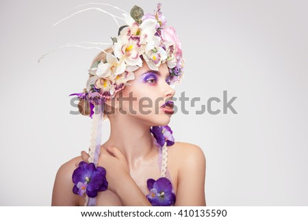 Beauty young woman with wreath on head and makeup in purple tones looking away in studio on grey background