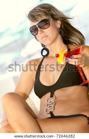 Beautyful woman enjoying her summer vacation with a glass of martini - stock photo