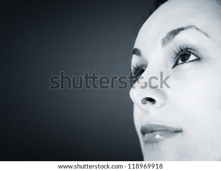 Beautyful woman looking up isolated on black background.