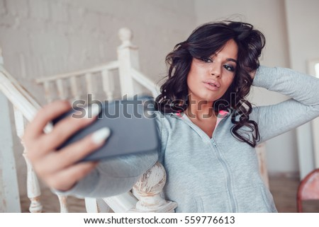 Beautyful young girl make selfie using smartphone at home.
