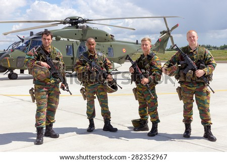 BEAUVECHAIN, BELGIUM - MAY 20, 2015: Belgian army soldiers in front of the new NH90 helicopter during the THPU exercise. THPU is an annual helicopter evaluation excercise.