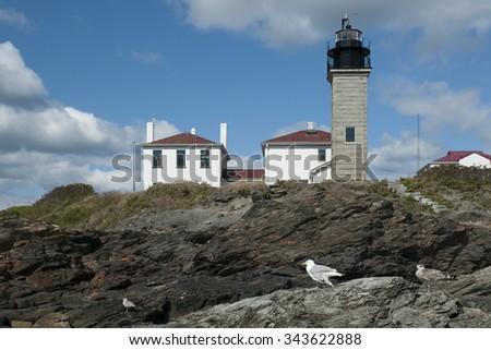 Beavertail lighthouse overlooks rocky coastline in Rhode Island. - stock photo